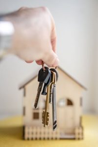 person holding a set of keys in front of a toy house